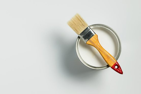 Paint brush placed on top of a can filled with white paint